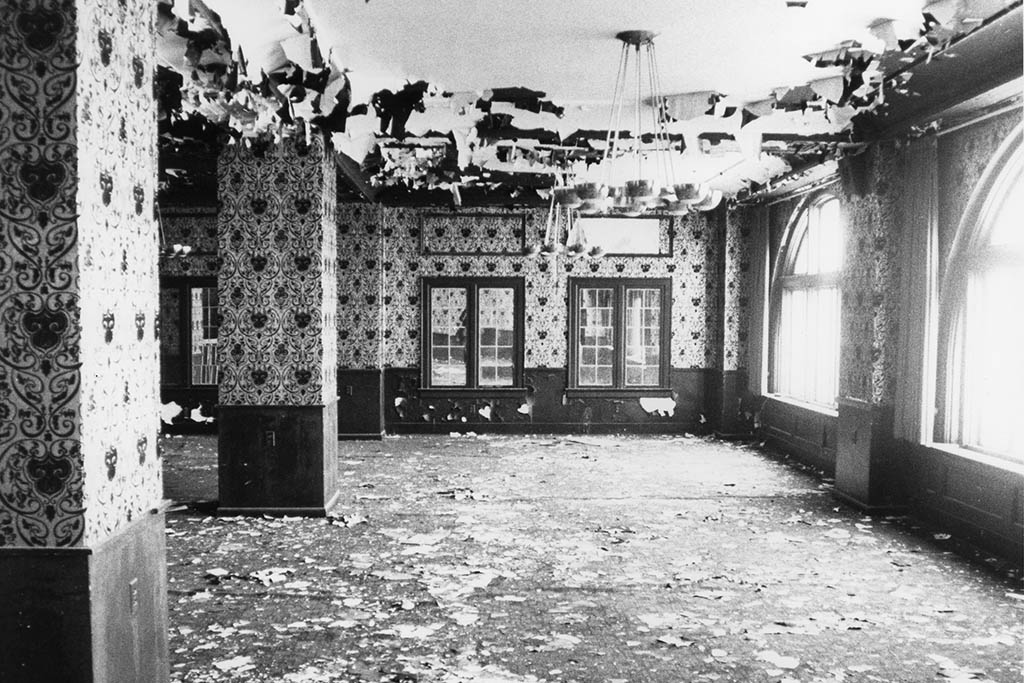 Graham Plaza interior prior to the renovation – paint pealing off the ceiling, pigeon manure everywhere, striped wallpaper, bunched up carpet, and more.