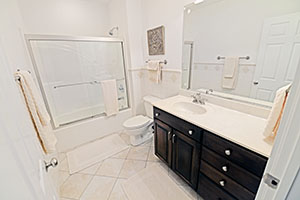 This spacious second bathroom has a neutral color palette of whites and creams and a complementary title floor.