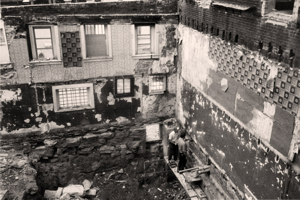 Photo shows three levels removed with two men standing in the bottom right working on repair needs.