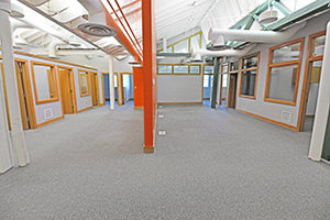 Extra large common area is divide by a bright orange partition.